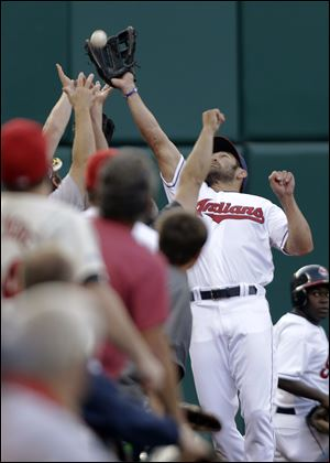 Cleveland Indians left fielder Johnny Damon leaps into the stands to catch a fo