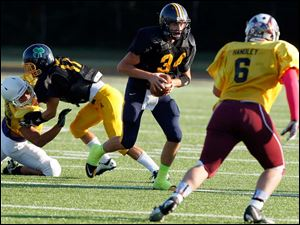 Black Squad quarterback Tyler Smith (34) of Whitmer High School runs the ball against the Gold Squad during the 22nd annual Regional All-Star Football Game Friday.
