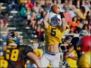 Gold Squad receiver Dylan Blunk (5) of Findlay High School makes a catch against the Black Squad during the 22nd annual Regional All-Star Football Game Friday.