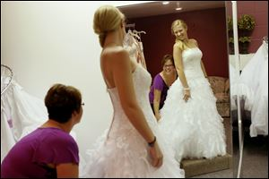 Morghan Spychalski and Paige LaCourse laugh as Spychalski tries on a Moonlight wedding dress at Dream Designs Bridal Outlet in Toledo.