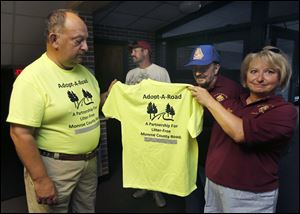 Phil Wesley, left, and Patti Wenski hold one of the shirts for volunteers such as Ms. Wenski and Ralph Wenski, center. They were at Our Lady of Mount Carmel last week.