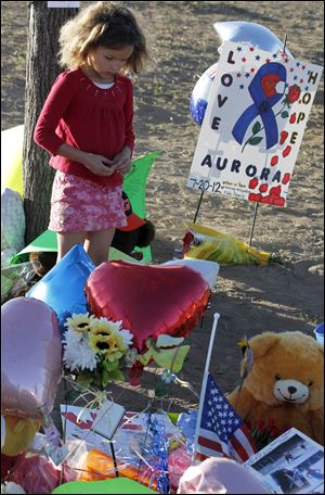 "Serenity Brydon, 7, from Aurora, looks at a memorial near the the Century 16 movie theater Sunday in Aurora, Colo. Twelve people were killed and dozens were injured in a shooting attack early Friday at the packed theater during a showing of the Batman movie, ""The Dark Knight Rises."""