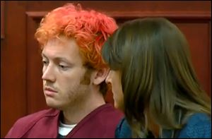 James Holmes, left, the suspected gunman in Friday's Colorado theater massacre, makes his first appearance in court with his attorney in Aurora, Colo.