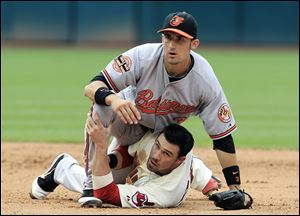 Baltimore second baseman Ryan Flaherty falls on Cleveland's Jason Kipnis after trying to turn a double play in the sixth inning.