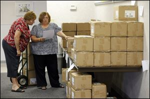 Brenda Mocek, left, and Kristina Schwarzkopf of the Toledo Federation of Teachers sort through materials provided by First Book.