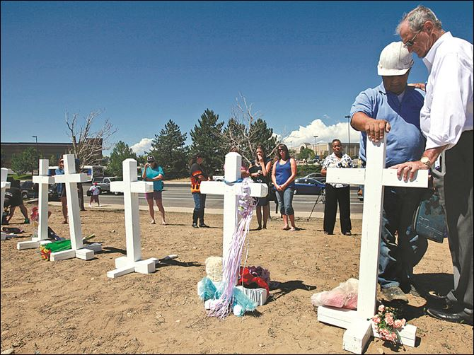 Colorado Shooting Columbine Crosses Steve Hogan, right, mayor of Aurora, Colo., where the movie theater attack took place, pauses to pray as Greg Zanis places a cross for the shooting victims. Mr. Zanis also placed crosses in 1999 for Columbine attack victims.