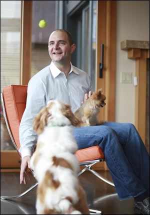 Aaron Easterly of Rover.com holds his dog Caramel as he pet sits Charlie. The site has about 10,000 hosts in more than 40 states.