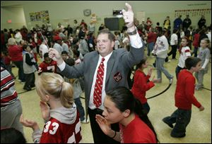Students and faculty at Crossgates Elementary School in Toledo form 'Script Ohio,' around Jon Waters during a visit by Mr. Waters and some of the band members to the school in November, 2007. Mr. Waters' mother, Cheryl, was a TPS teacher and administrator.