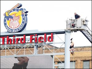 A member of the Toledo Fire & Rescue repels from a ladder track in the outfield before the Mud Hens' game.