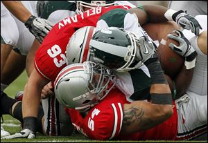 John Simon (54) wraps up Michigan State running back Edwin Baker during a game last season in Columbus. Simon had seven sacks and 17 tackles for a loss last year to earn All-Big Ten honors.