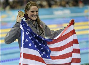 Missy Franklin, a 17-year-old phenom, clutches the American flag and her first gold medal after winning the 100-meter backstroke.