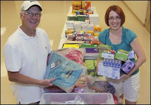 Holland Free Methodist Church administrator Mike Yunker and project coordinator Christy Winckles organize the back-to-school supplies the church will make available at no charge Aug. 8 to children in need.
