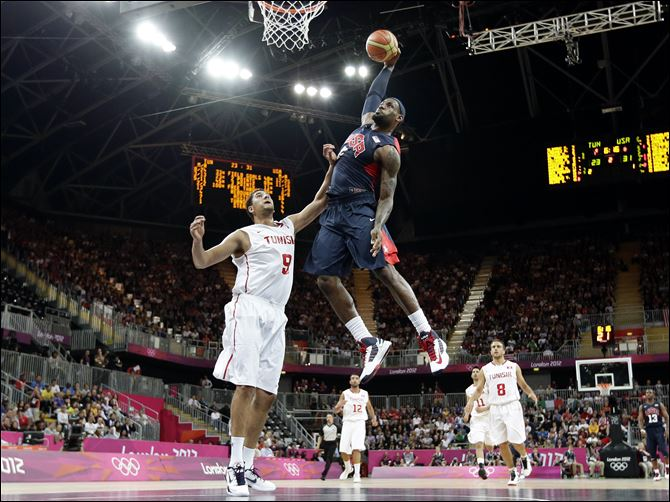 London Olympics Basketball Men USA's Lebron James, right, dunks over Tunisia's Mohamed Hadidane, left, during the first half of a preliminary men's basketball game at the 2012 Summer Olympics, Tuesday.