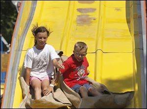 Autumn Ehrsam, 10, and her brother Levi Ehrsam, 8, of Delta go down the slide.