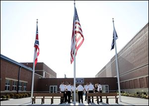 The flags are raised during a tour today of the new Lake High School.