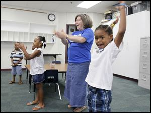 Jermarianhne Morgan, 5, joins substitute teacher Janice Zraik, and his classmates, in an educational activity.