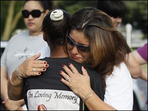 Demisha Wilborn, left, gets a hug from Trina Oviedo-Frankum during a vigil at the Violence Against Women Memorial Rock at the Sanger Branch of the library, Thursday, August 2, 2012. Wilborn's daughter Tiffany Wilborn was killed as a result of a March 11 attack, while Oviedo-Frankum's daughter Leandra Frankum was killed on July 22.