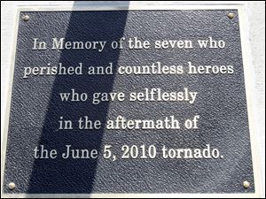 A plaque under the flagpoles at the school honors those who died and those who made other sacrifices.