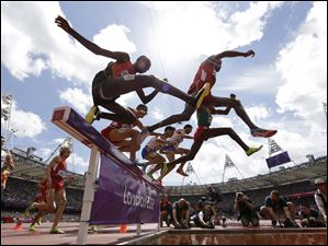 Athletes clear a barrier in the men's steeplechase.