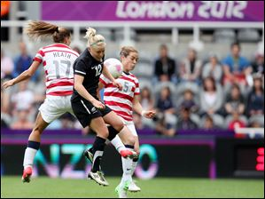 New Zealand's Betsy Hassett, center, vies for the ball with United States' Tobin Heath, left, and Kelley O Hara, right, during the women's quarter-final soccer match at St James' Park in Newcastle, England.