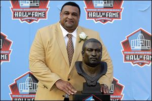 Former Saints lineman Willie Roaf poses with his bust that will sit inside the NFL Hall of Fame in Canton.