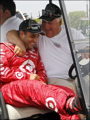 Juan Pablo Montoya, left, receives a hug after winning the pole for today's race in Long Pond, Pa.