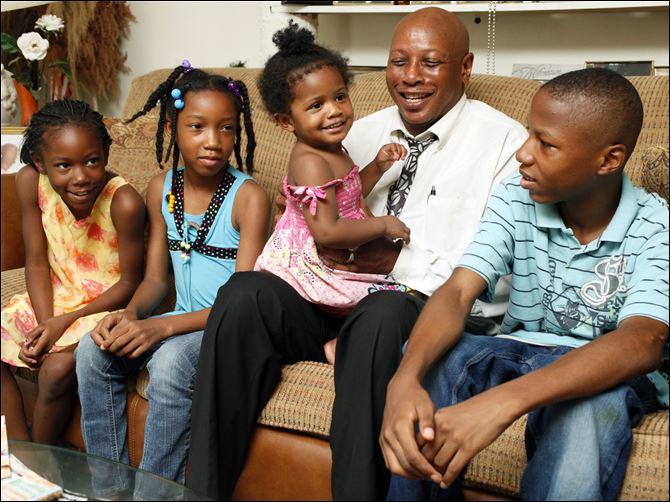 CTY kinship05p Roy Jenkins of North Toledo is raising not only his daughter R'Zhanai, on his lap, but also three of his grandchildren. Seated on the couch from left are granddaughters Doreanna, 8, and Heaven, 10, and grandson JayVon, 13.