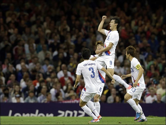 South Korea's Ji Dong-won (9) celebrates his goal with teammates Yun Suk-young (3), Koo Ja-cheol (13), and Ki Sung-yueng (6).