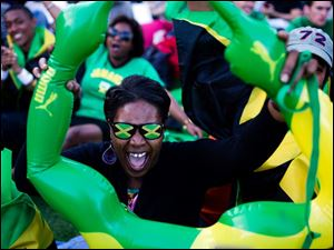 A Jamaica supporter reacts as she watches a broadcast of the men's 100-meter semifinals on a screen at the Puma Yard in London during the 2012 Summer Olympics.