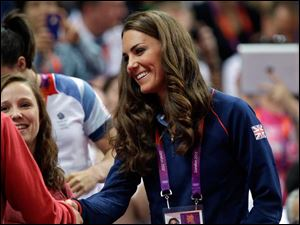 Kate, Duchess of Cambridge, speaks to a spectator during the artistic gymnastics apparatus finals.