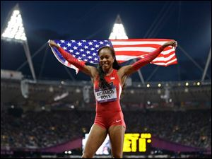 Sanya Richards Ross from the U.S. holds her national flag and celebrates after winning the women's 400-meter final.