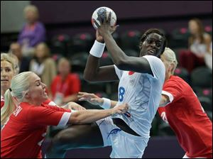 Denmark's Trine Troelsen, left, tries to stop France's Claudine Mendy during their women's handball preliminary match.