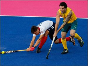 Britain's Lain Mackay, left, and Australia's vie Lain Mackay vie for the ball in a men's hockey preliminary match.
