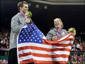 Mike Bryan and Lisa Raymond of the United States celebrate their bronze medals in mixed doubles at the All England Lawn Tennis Club in Wimbledon.