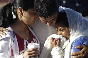Amardeep Kaleka, son of the president of the Sikh Temple of Wisconsin, center, comforts members of the temple in Oak Creek, Wis., where a gunman killed six people a day earlier, before being shot and killed himself by police.