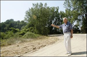 Howard Pinkley, of Point Place, points out the future location of his envisioned restaurant and lodge along the mile-long pathway that he is also planning to build on the forested peninsula adjacent to the Toledo Yacht Club.