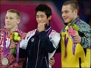 South Korean gold medallist gymnast Yang Hak-seon , center, Russia's silver medallist Denis Ablyazin, left, and Ukraine's bronze medallist Igor Radivilov celebrate on the podium during the artistic gymnastics men's apparatus finals.