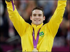 Brazilian gymnast Arthur Nabarrete Zanetti celebrates on the podium after receiving the gold for his performance on the rings.