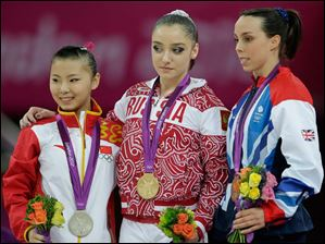 Russian gold medallist gymnast Aliya Mustafina, center, Chinese silver medallist He Kexin, left, and Britain's bronze medallist Elizabeth Tweddle stand during the podium ceremony for the uneven bars during the artistic gymnastics women's apparatus finals.