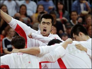China's Zhang Zhaoxu pumps his fist while huddling with teammate prior to facing Britain in men's basketball.