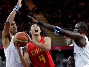 China's Ding Jinhui (4) drives between Great Britain defenders Kieron Achara, left, and Luol Deng, right, during a preliminary men's basketball game.