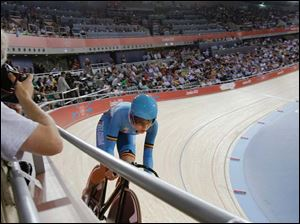 A photographer takes pictures of Belgium's Jolien D'Hoore as she competes in the women's omnium flying lap event.