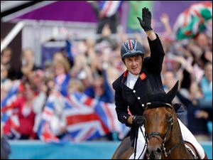 Peter Charles, of Great Britain, waves to the fans after riding Vindicat to a gold medal during the equestrian show jumping team competition.