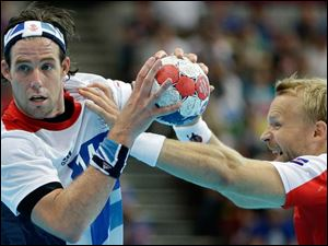 Britain's Steven Larsson, left, and Iceland's Ingimundur Ingimundarson challenge during their men's handball preliminary match.