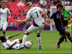 Japan's Shinobu Ohno, right, challenges for the ball with France's Corine Franco, center, and France's Laura Georges during the women's soccer semifinal match between Japan and France.