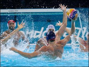Jeff Powers, No 4 blue cap,of the United States finds his opening for a shot on goal guarded  by Peter Biros of Hungary, in front of him,during their men's water polo preliminary round match.