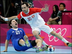 Croatia's Ivan Cupic, left, is fouled by Tunisia's Heykel Megannem during their men's handball quarterfinal match.