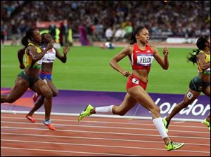 United States' Allyson Felix, center, goes for the finish line to win gold ahead of Jamaica's Shelly-Ann Fraser-Pryce, right, in the women's 200-meter final.