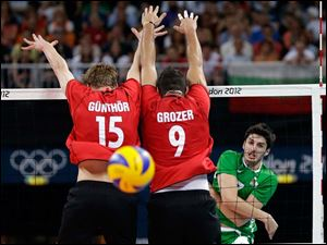Bulgaria's Todor Skrimov (7, right) spikes the ball past Germany defenders Max Gunthor (15)  and Gyorgy Grozer (9) during a men's volleyball quarterfinal match.