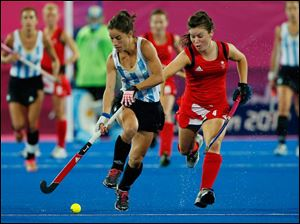 Britain's Laura Unsworth and Argentina's Rosario Luchetti, left, vie for the ball during a women's hockey semifinal match.